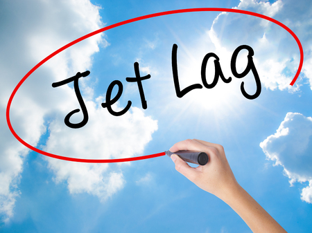 Woman Hand Writing  Jet Lag with black marker on visual screen. Isolated on Sunny Sky. Business concept. Stock Photo