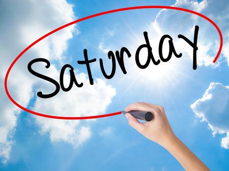 女性の手書きビジュアル画面に黒のマーカーで土曜日。晴れた空上に分離。ビジネス、技術、インターネットの概念。