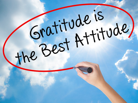 Woman Hand Writing Gratitude is the Best Attitude with black marker on visual screen. Isolated on Sunny Sky. Business concept. Stock Photo