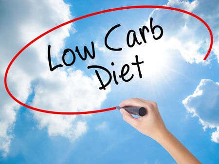 Woman Hand Writing Low Carb Diet with black marker on visual screen. Isolated on Sunny Sky. Business concept. Stock Photo