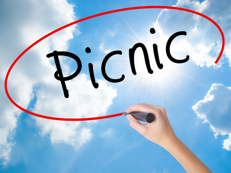picknick: Woman Hand Writing Picnic with black marker on visual screen. Isolated on Sunny Sky. Business concept. Stock Photo