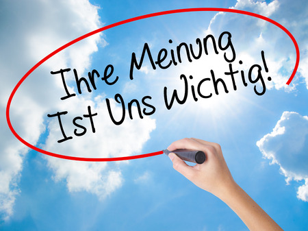 Woman Hand Writing Ihre Meinung Ist Uns Wichtig! (Your Opinion is Important to Us in German) with marker on visual screen. Isolated on Sunny Sky. Business concept. Stock Photo Stock Photo