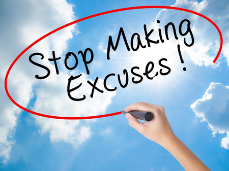 Woman Hand Writing Stop Making Excuses with black marker on visual screen. Isolated on Sunny Sky. Business concept. Stock Photo