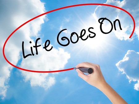 trouble free: Woman Hand Writing Life Goes On with black marker on visual screen. Isolated on Sunny Sky. Business concept. Stock Photo Stock Photo