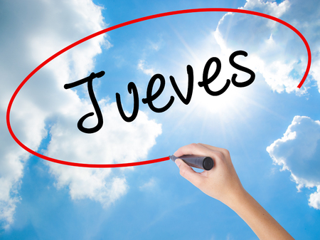 Woman Hand Writing Jueves (Thursday in Spanish) with black marker on visual screen. Isolated on Sunny Sky. Business concept. Stock Photo