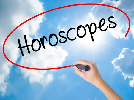 Woman Hand Writing Horoscopes  with black marker on visual screen. Isolated on Sunny Sky. Business concept. Stock Photo