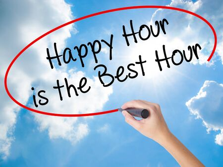 Woman Hand Writing Happy Hour is the Best Hour  with black marker on visual screen. Isolated on Sunny Sky. Business concept. Stock Photo