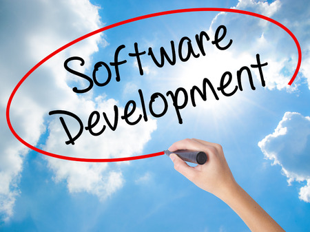 Woman Hand Writing Software Development with black marker on visual screen. Isolated on Sunny Sky. Business concept. Stock Photo