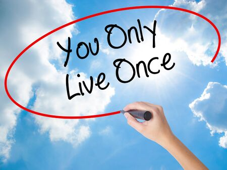 Woman Hand Writing You Only Live Once with black marker on visual screen. Isolated on Sunny Sky. Business concept. Stock Photo Stock Photo