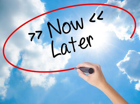 Woman Hand Writing NowLater with black marker on visual screen. Isolated on Sunny Sky. Business concept. Stock Photo