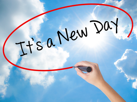 Woman Hand Writing Its a New Day with black marker on visual screen. Isolated on Sunny Sky. Business concept. Stock Photo Stock Photo
