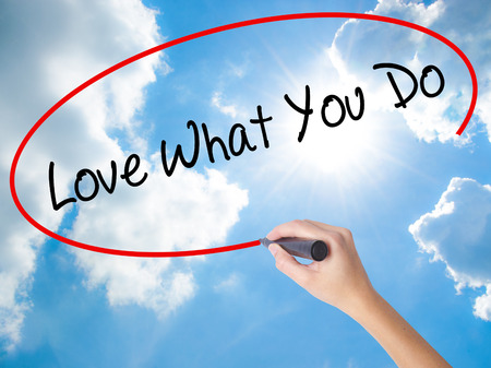 Woman Hand Writing Love What You Do with black marker on visual screen. Isolated on Sunny Sky. Business concept. Stock Photo Stock Photo