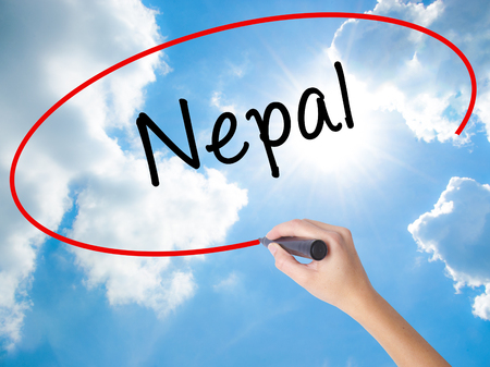 Woman Hand Writing Nepal  with black marker on visual screen. Isolated on Sunny Sky. Business concept. Stock Photo Stock Photo