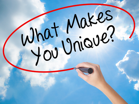 Woman Hand Writing What Makes You Unique? with black marker on visual screen. Isolated on Sunny Sky. Business concept. Stock Photo