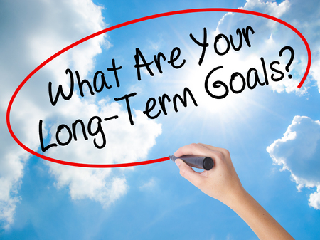 Woman Hand Writing What Are Your Long-Term Goals? with black marker on visual screen. Isolated on Sunny Sky. Business concept. Stock Photo Stock Photo