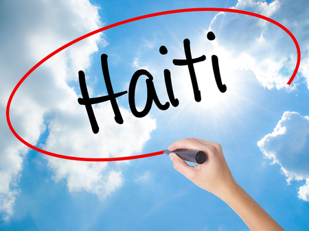 Woman Hand Writing Haiti with black marker on visual screen. Isolated on Sunny Sky. Business concept. Stock Photo