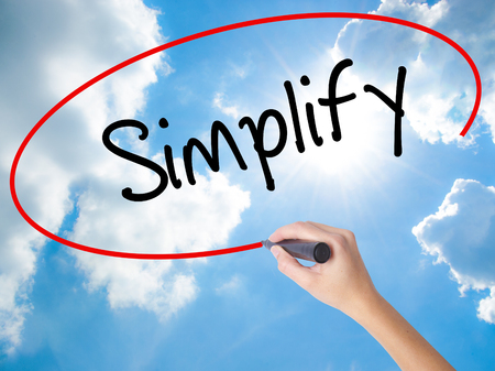Woman Hand Writing Simplify with black marker on visual screen. Isolated on Sunny Sky. Business concept. Stock Photo Stock Photo
