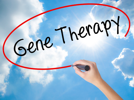 Woman Hand Writing Gene Therapy with black marker on visual screen. Isolated on Sunny Sky. Business concept. Stock Photo Stock Photo