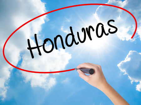 Woman Hand Writing Honduras with black marker on visual screen. Isolated on Sunny Sky. Business concept. Stock Photo