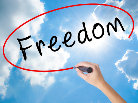 Woman Hand Writing Freedom with black marker on visual screen. Isolated on Sunny Sky. Business concept. Stock Photo