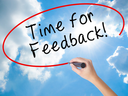 Woman Hand Writing Time for Feedback with black marker on visual screen. Isolated on Sunny Sky. Business concept. Stock Photo Stock Photo