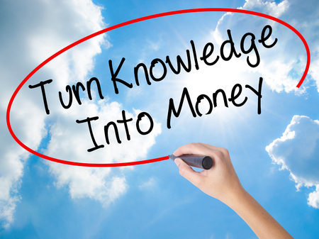 Woman Hand Writing Turn Knowledge Into Money with black marker on visual screen. Isolated on Sunny Sky. Business concept. Stock Photo Stock Photo