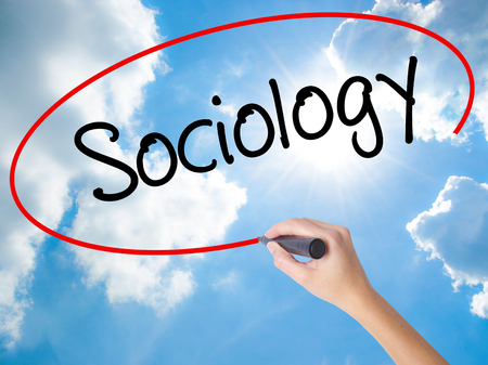 Woman Hand Writing Sociology  with black marker on visual screen. Isolated on Sunny Sky. Business concept. Stock Photo
