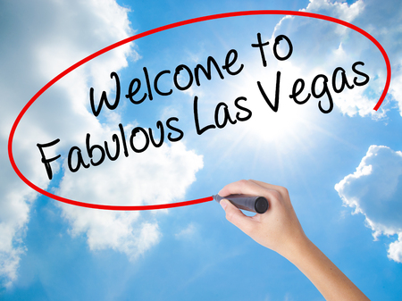 Woman Hand Writing Welcome to Fabulous Las Vegas with black marker on visual screen. Isolated on Sunny Sky. Business concept. Stock Photo