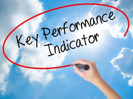 Woman Hand Writing Key Performance Indicator with black marker on visual screen. Isolated on Sunny Sky. Business concept. Stock Photo Stock Photo