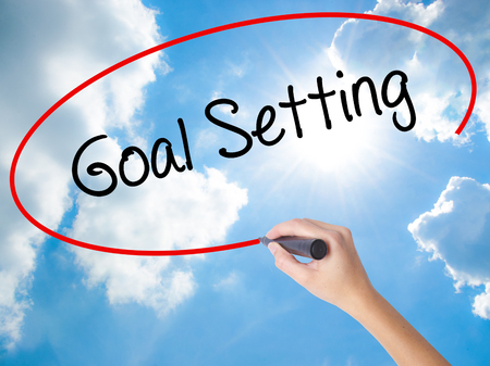 Woman Hand Writing Goal Setting  with black marker on visual screen. Isolated on Sunny Sky. Business concept. Stock Photo