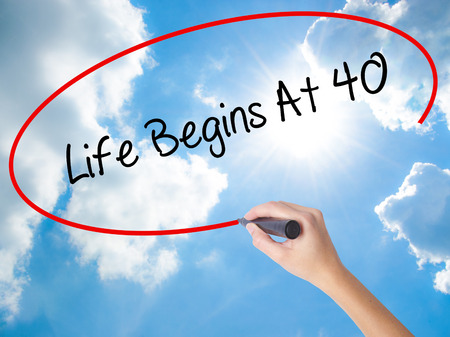 Woman Hand Writing Life Begins At 40  with black marker on visual screen. Isolated on Sunny Sky. Business concept. Stock Photo
