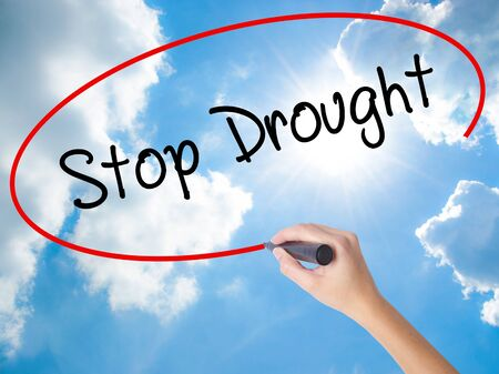 Woman Hand Writing  Stop Drought with black marker on visual screen. Isolated on Sunny Sky. Business concept. Stock Photo Stock Photo