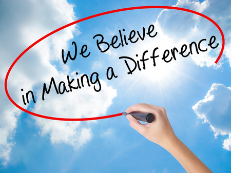 Woman Hand Writing We Believe in Making a Difference with black marker on visual screen. Isolated on Sunny Sky. Business concept. Stock Photo