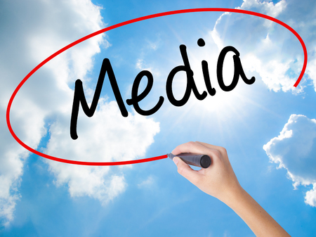 Woman Hand Writing Media with black marker on visual screen. Isolated on Sunny Sky. Business concept. Stock Photo