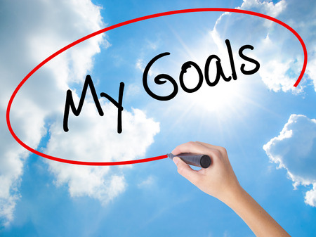 specific: Woman Hand Writing  My Goals with black marker on visual screen. Isolated on Sunny Sky. Business concept. Stock Photo