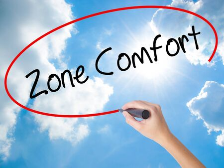 Woman Hand Writing Zone Comfort with black marker on visual screen. Isolated on Sunny Sky. Business,  internet concept. Stock Photo