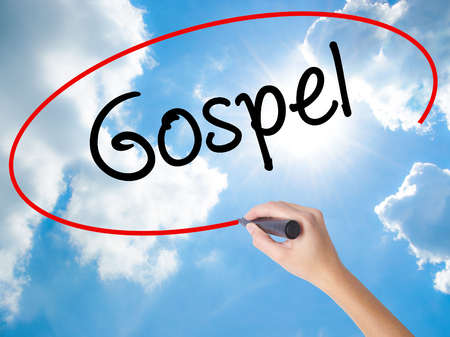 Woman Hand Writing Gospel  with black marker on visual screen. Isolated on Sunny Sky. Business concept. Stock Photo