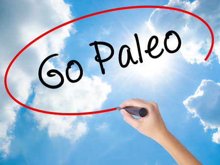 Woman Hand Writing Go Paleo with black marker on visual screen. Isolated on Sunny Sky. Business concept. Stock Photo