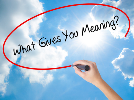 Woman Hand Writing What Gives You Meaning? with black marker on visual screen. Isolated on Sunny Sky. Business concept. Stock Photo