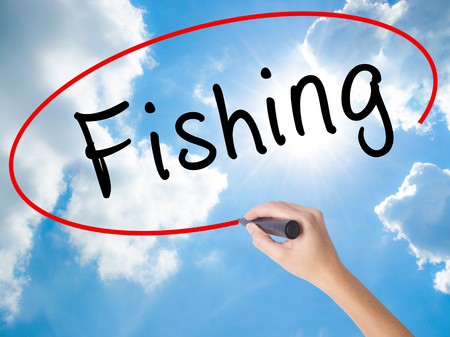 Woman Hand Writing Fishing with black marker on visual screen. Isolated on Sunny Sky. Business concept. Stock Photo Stock Photo