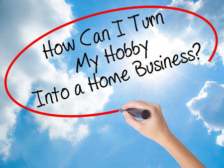 owning: Woman Hand Writing How Can I Turn My Hobby Into a Home Business? with black marker on visual screen. Isolated on Sunny Sky. Business concept. Stock Photo