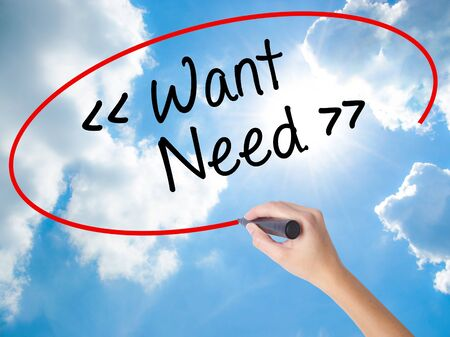 Woman Hand Writing Want - Need  with black marker on visual screen. Isolated on Sunny Sky. Business concept. Stock Photo