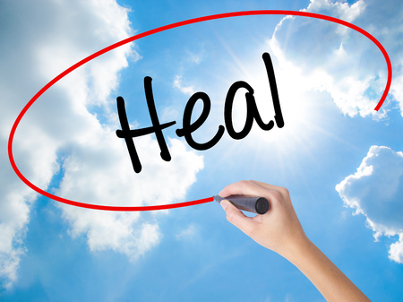 complementary therapies: Woman Hand Writing  Heal  with black marker on visual screen. Isolated on Sunny Sky. Business concept. Stock Photo