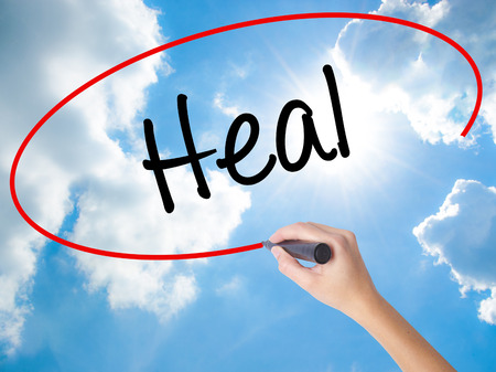 healer: Woman Hand Writing  Heal  with black marker on visual screen. Isolated on Sunny Sky. Business concept. Stock Photo