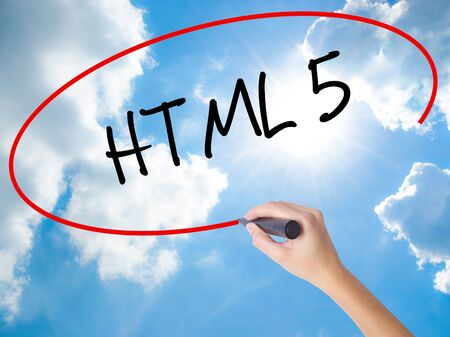 Woman Hand Writing HTML 5 with black marker on visual screen. Isolated on Sunny Sky. Business concept. Stock Photo Stock Photo
