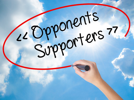 either: Woman Hand Writing Opponents - Supporters with black marker on visual screen. Isolated on Sunny Sky. Business concept. Stock Photo