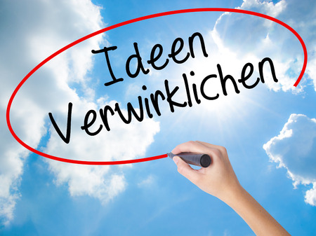 revelation: Woman Hand Writing Ideen Verwirklichen ( Realize Ideas in German) with black marker on visual screen. Isolated on Sunny Sky. Business concept. Stock Photo