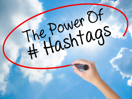 keyword research: Woman Hand Writing The Power of Hashtags with black marker on visual screen. Isolated on Sunny Sky. Business concept. Stock Photo
