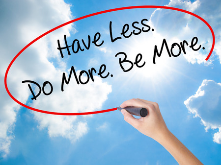 humility: Woman Hand Writing Have Less. Do More. Be More.  with black marker on visual screen. Isolated on Sunny Sky. Business concept. Stock Photo
