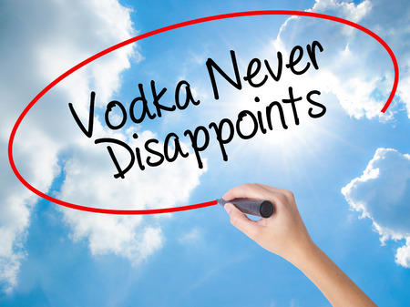 Woman Hand Writing Vodka Never Disappoints with black marker on visual screen. Isolated on Sunny Sky. Business, technology, internet concept.